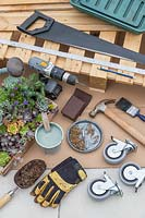 Tools and materials for creating a succulent plant pallet table on castors.