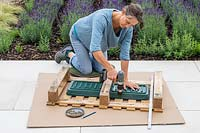 Woman drilling through edge of plastic plant tray to be fitted on the underside of pallet to contain the compost and plants.