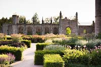 Parterre with low blocks of Taxus - Yew - framing herbaceous perennials including Filipendula venusta 'Rubra' and Veronicastrum virginicum 'Spring Dew', castle behind