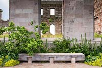 Oak bench in front of castle ruin surrounded by Acanthus mollis Latifolius Group 'Rue Ledan', Alchemilla mollis, Jasminum officinale 'Devon Cream' and Cercis canadensis f. alba 'Royal White'