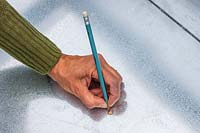 Woman using a pencil to mark holes for drainage