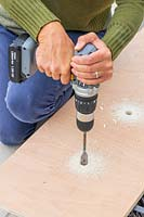 Woman using cordless electric drill to create drainage holes in wooden base for planter