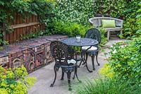 Wrought Iron Table and chairs in suburban garden with feature gabion baskets filled with roof tiles and pipes