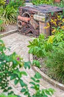 Brick path ending with feature gabion filled with assorted rooding tiles and pipes