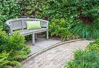 View along brick paving towards rustic wooden bench with green cushion in front of fence covered with Trachelospermum jasminoides - Star jasmine
