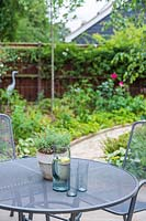 View of suburban garden from metal dining table and chairs