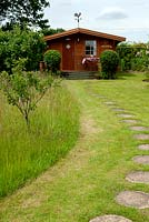 Tall grass around fruit trees left for the benefit of wildlife and insects, with path of stepping stones leading to distant summerhouse - Open Gardens Day, Kelsale, Suffolk