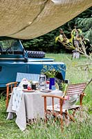 Table and chairs set for picnic, landrover in background