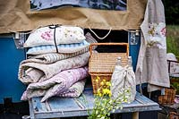 Bundle of vintage floral cushions and blankets at the back of landrover