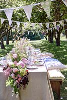 Summer table setting in orchard with central floral arrangement and bunting