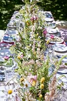 Summer table setting in orchard with central floral arrangement