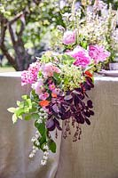 Floral arrangement hanging over the end of the table, flowers include roses, elderflower, Deutzia nad Cotinus