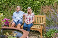 Garden owners sat on bench by corten steel water feature