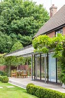 Patio and metal pergola with climbers running along house, edged with Buxus hedging