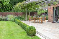 Sandstone Patio and metal and wood pergola with climbers running along house, edged with Buxus hedging, wooden dining furniture