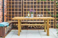 Wooden dining table and bench with built in storage for firewood, backed by fence with trellis