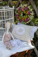Floral wreath, bird cage, pillows and a rag doll on wooden table against a wooden lattice fence