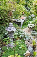 Small oriental and tropical garden with hammock, ornaments and mixed planting