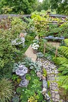 View of garden from above showing path leading through mixed planting to seating area by shed and hammock