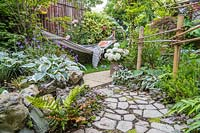 Small suburban garden with crazy paving path, bamboo fencing and view to hammock