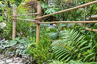 Simple bamboo fencing along edge of path with mixed planting