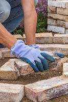 Woman wearing gloves placing bricks in a a spiral shape