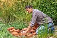 Woman placing red bricks in circle in gravel garden