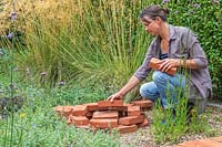 Woman adding bricks to the centre of the tower to create stability