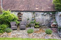 Cobbled farmyard with pots of lavender, table with display of succulents,  galvanised gardenalia, a stone drinking trough and seating