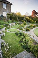 A view from the upper terrace across curving walls, lawns and borders towards clipped shrubs and lawn below.