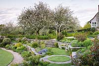 Terraces of planting with an orchard of blossoming fruit trees beyond in May