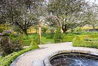 Circular pond with water spouts on the terrace with orchard of flowering fruit trees beyond