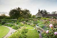Terraces planted with roses, lavender, herbaceous perennials and shrubs in June