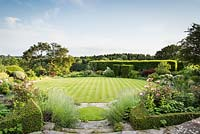 Steps between box hedges containing roses and lavender lead down to a circular lawn surrounded by borders of shrubs and herbaceous perennials and a hornbeam allee