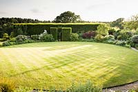 Circular lawn surrounded by borders of shrubs and perennials,