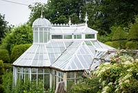 Rare Mackenzie and Moncur glasshouse surrounded by clipped evergreens and lush planting in the walled garden