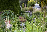 Walled garden in June full of lush planting, containers and structures including a tea house on stilts