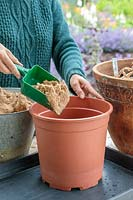 Woman using green plastic scoop to add sand to large plastic pot