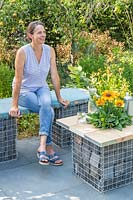 Woman sitting on gabion and scaffolding board bench, that is complimented by a matching table on slate patio in modern garden.