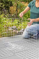 Woman using spiral helicoils to join components of gabion basket