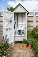 Mini wooden garden shed filled with garden tools