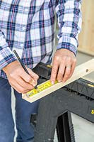 Using a pencil and tape measure to mark where to cut timber