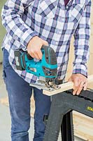 Using a cordless jigsaw to cut timber battens to size