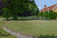 View over lawn to 16th century ochre-washed farmhouse with flint Ha-ha.