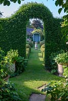 View through clipped Taxus baccata - Yew arch to The Secret Garden with Sundial and clipped Buxus - box hedges.