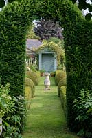 View through Taxus baccata - Yew arch to The Secret Garden with Sundial and clipped Buxus - box hedges and balls.
