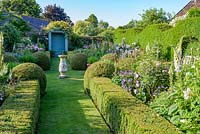The Secret Garden with Sundial and clipped Buxus - box hedges and balls.