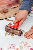 Woman rolling leaves painted with metallic spray paints onto paper bags using a lino roller.