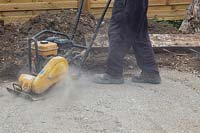 Man compressing foundation of crushed concrete for patio with compaction plate.