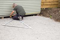 Man measuring space for patio with tape measure.